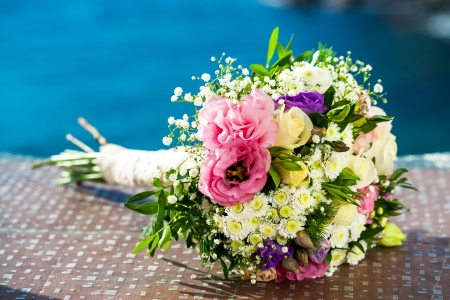 24896618 - colorful bridal flower bouquet outdoors with blue background.