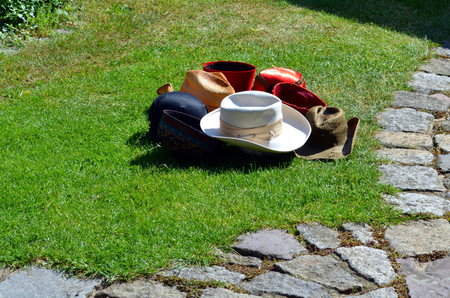 55454086 - bunch of differtent hats lying in grass